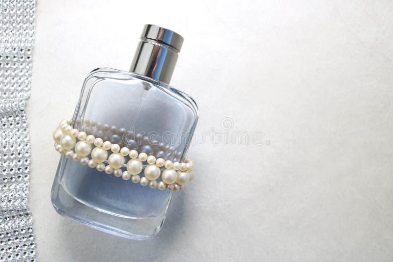 Błękitna piękna szklana przejrzysta modna wspaniała butelka cologne, pachnidło z białymi klejnotami i miejsce dla prostego teksta zdjęcia stock