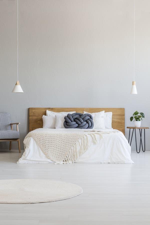 Błękitna poduszka na białym łóżku z drewnianym headboard w hotelowej sypialni zdjęcie stock