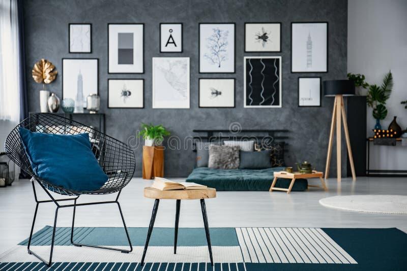 Błękitna poduszka na karle obok stołu w żywym izbowym wnętrzu z futon i plakatami Istna fotografia z zamazanym tłem obraz royalty free