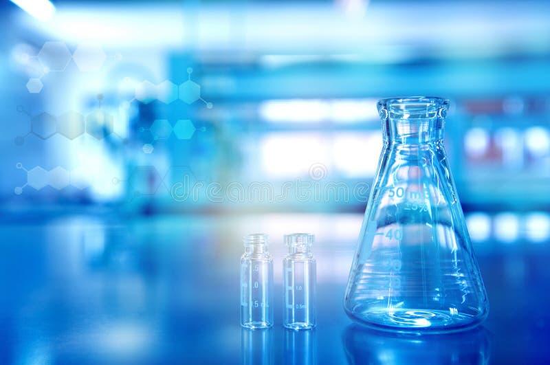 Błękitna szklana kolba z buteleczką w badawczym chemii nauki laborat zdjęcie stock
