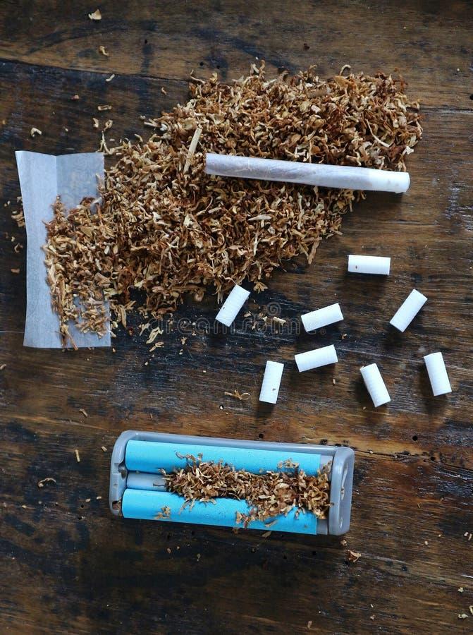 Błękitna toczna maszyna z filtrowymi poradami i handmade papieros na tabacznym rozsypisku zdjęcie stock