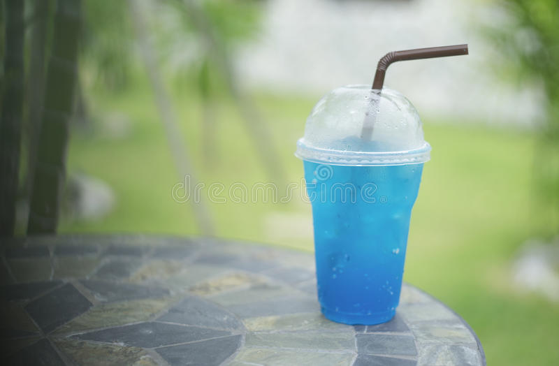 Błękitna włoska soda w takeaway filiżance na marmuru kamienia stole z zamazaną zieloną trawą i bambusem w tle, selekcyjna ostrość zdjęcia stock