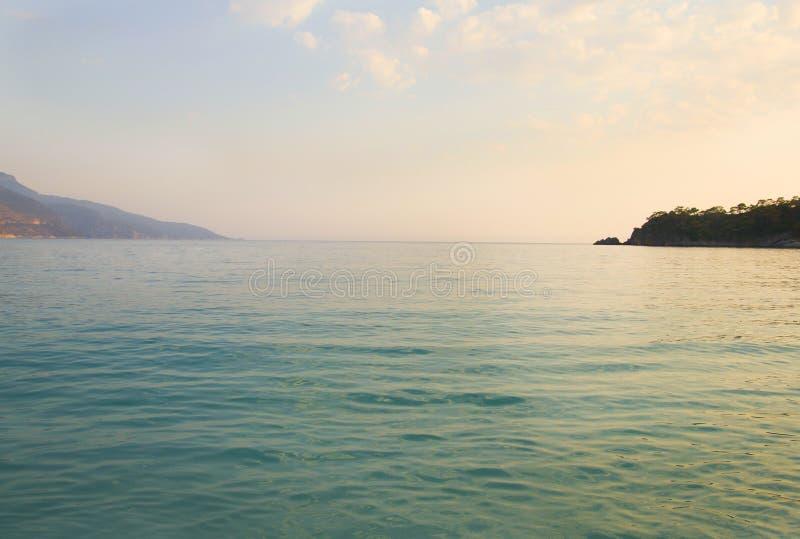 Błękitne wody przy nadmorski z białymi otoczakami fotografia stock
