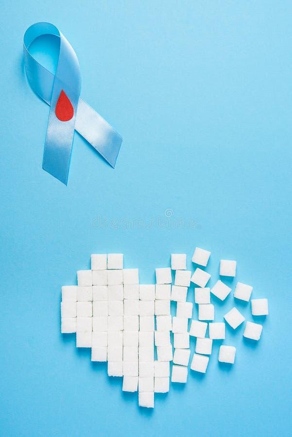Błękitnego faborku świadomość z czerwoną krwi kroplą i złamane serce robić cukrowi sześciany na błękitnym tle, światowy cukrzyca  zdjęcia stock