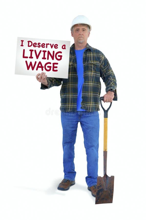 Błękitnego kołnierza pracownika budowlanego mężczyzna trzyma znaka mówi w ciężkim kapeluszu z łopatą Zasługuję ŻYWĄ płacę fotografia stock