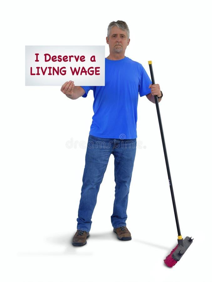 Błękitnego kołnierza pracownika mężczyzna trzyma znaka mówi z pchnięcie miotłą Zasługuję ŻYWĄ płacę zdjęcia stock
