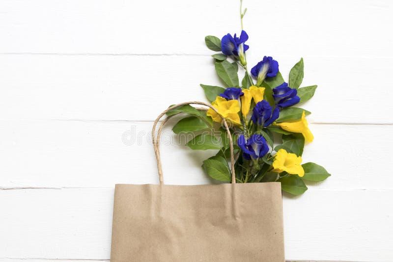 Błękitnego kwiatu motyli groch i żółty kwiat w papierowej torbie obrazy royalty free
