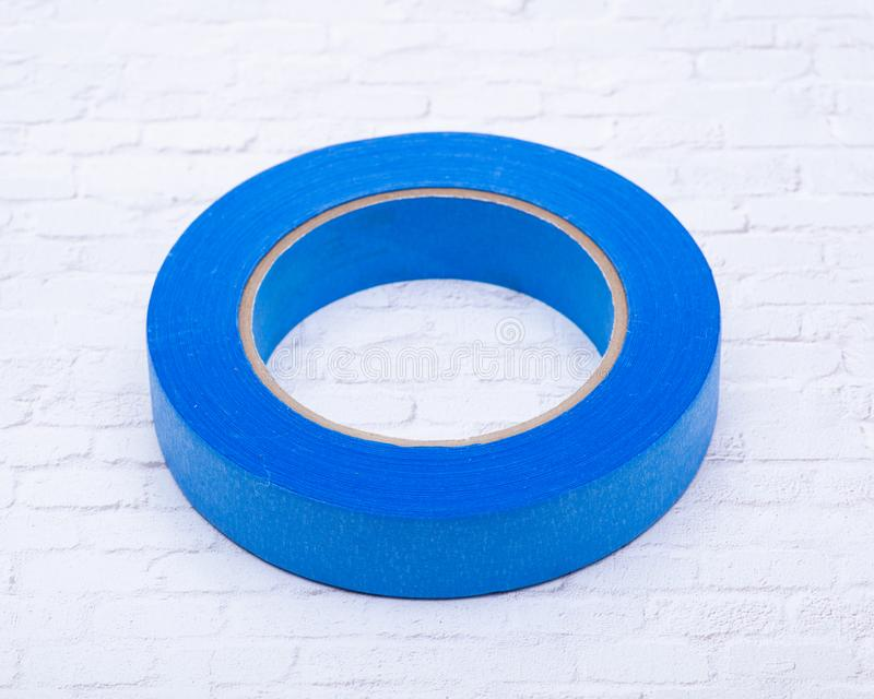 Błękitnego malarza taśma dla wielo- powierzchni odizolowywać na białej ścianie z cegieł zdjęcie stock