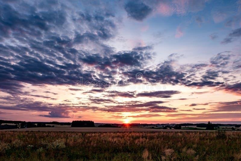 Błękitnej czerwieni nieba tło z wieczór puszystym kędzierzawym kołysaniem się chmurnieje z położenia słońcem Dobra wietrzna pogod obraz stock