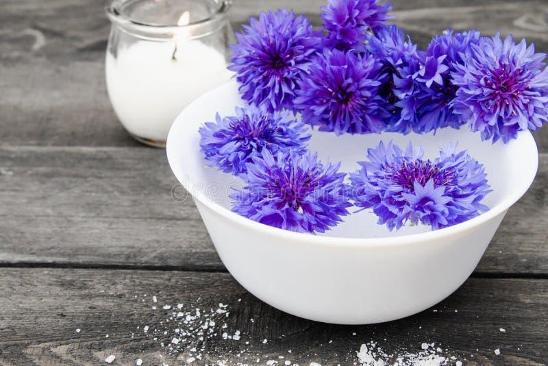 Błękitni cornflowers kłamają w wodzie w białym pucharze blisko płonącej świeczki na tle stare deski zdjęcie stock