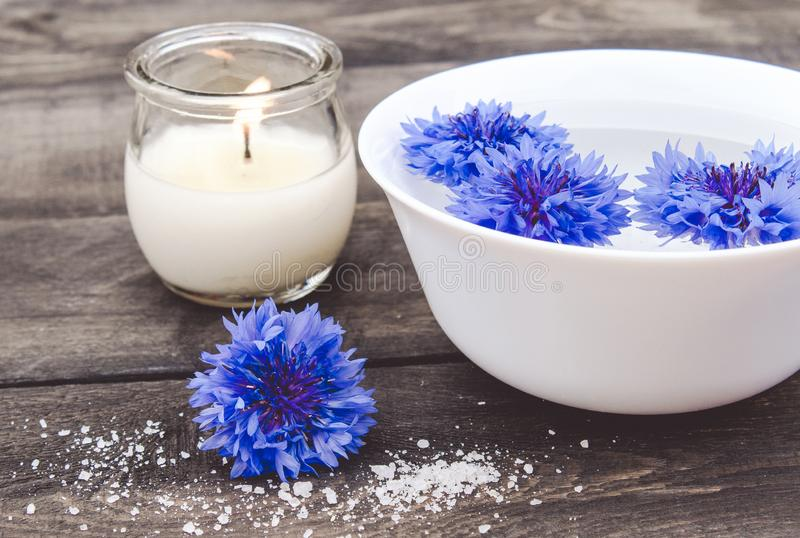 Błękitni cornflowers kłamają w wodzie w białym pucharze blisko płonącej świeczki na tle stare deski obrazy royalty free