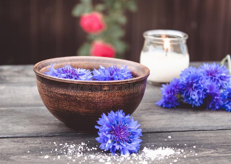 Błękitni cornflowers kłamają w wodzie w białym pucharze blisko płonącej świeczki na tle stare deski fotografia royalty free
