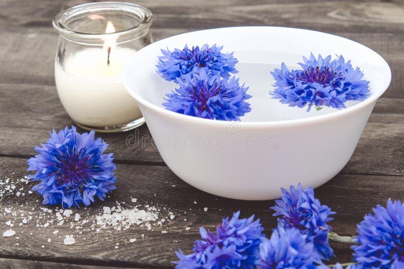 Błękitni cornflowers kłamają w wodzie w białym pucharze blisko płonącej świeczki na tle stare deski obrazy stock