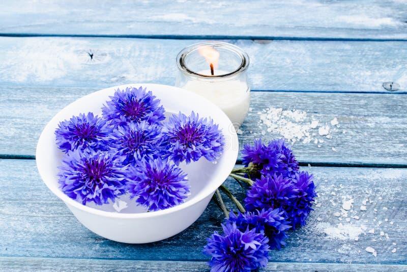 Błękitni cornflowers kłamają w wodzie w białym pucharze blisko płonącej świeczki przeciw tłu błękitne stare deski obrazy stock