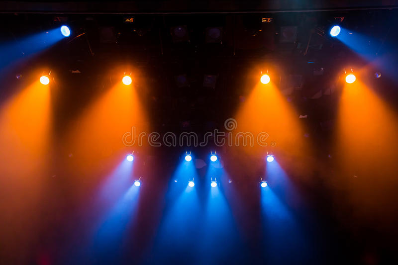 Błękitni i pomarańczowi promienie światło przez dymu na scenie Zaświecający equipment Światło zdjęcia stock