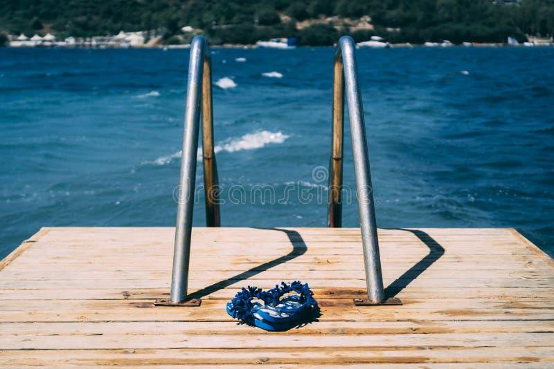 Błękitni lato sandały na drewnianym doku z błękitnym morzem w tle zdjęcie royalty free