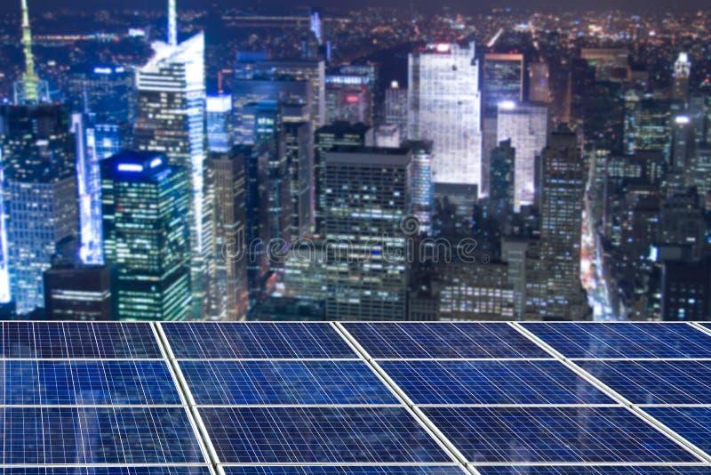 Błękitni ogniwo słoneczne panel, Nowy Jork pejzaż miejski iluminujący przy nocą obraz royalty free