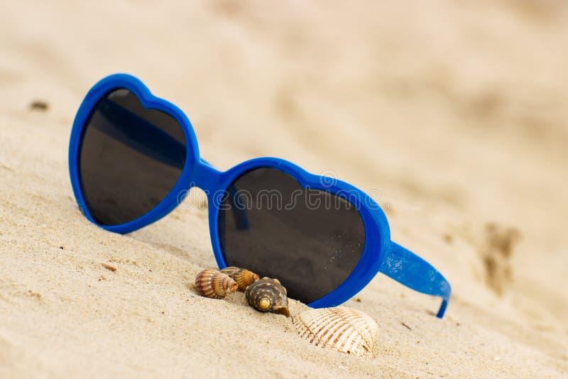 Download Błękitni Okulary Przeciwsłoneczni Kształtowali Serce Z Skorupami Na Piasku Obraz Stock - Obraz złożonej z foremność, romantyczny: 57654693