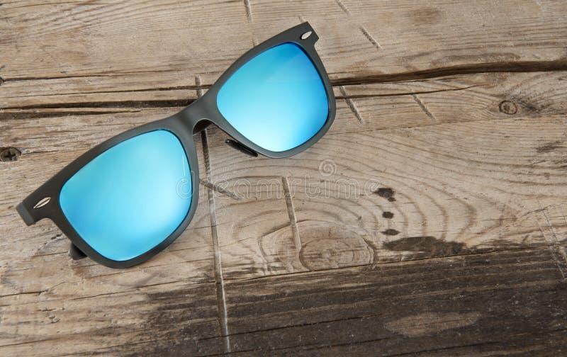 Błękitni okulary przeciwsłoneczni na drewnianym tle fotografia royalty free
