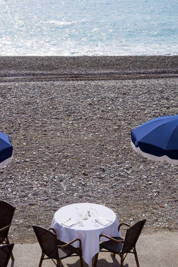 Błękitni parasole, rezerwujący stoły z białymi tablecloths na otoczak plaży Promenade Des Anglais w Ładnym, Francja, oczek fotografia royalty free