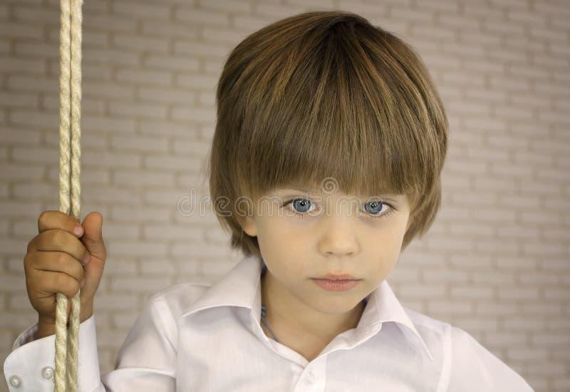 Błękitnooka chłopiec w białej koszula z arkaną zdjęcie royalty free