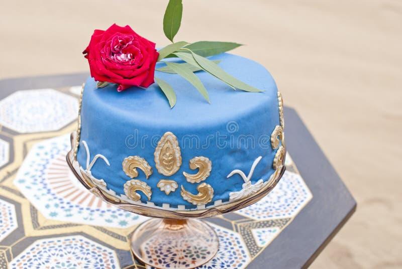 Błękitny ślubny tort na stołowych i czerwonych różach na wierzchołku obraz stock