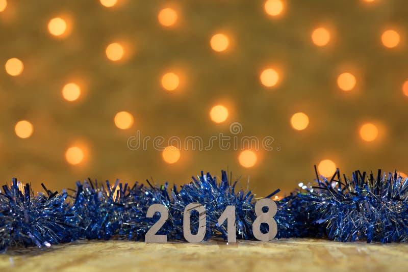 Błękitny świecidełko z postaciami 2018 na stole na tle nowego roku ` s girlanda z złotymi światłami obraz royalty free