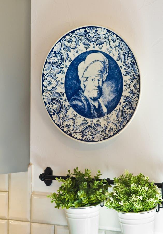 Błękitny ceramiczny talerz z rocznika portretem, houseplants i zdjęcia stock