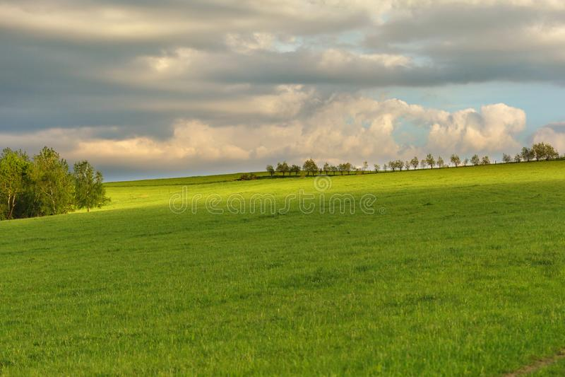 Błękitny chmurny niebo nad zielonymi wzgórzami i odległymi drzewami obrazy stock