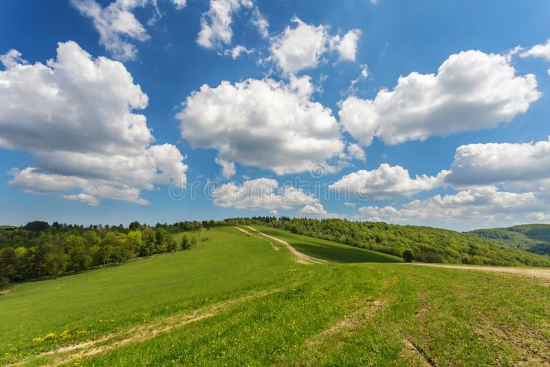 Błękitny chmurny niebo nad zielonymi wzgórzami i wiejską drogą obraz stock