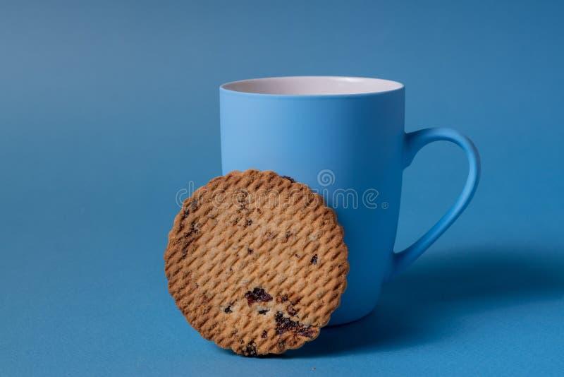 Błękitny ciastko na błękitnym tle i kubek obraz stock