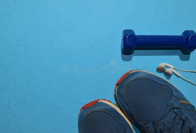 Błękitny dumbbell, sneakers i słuchawka treningu wskazujący plan na błękitnym tle, zdjęcie stock