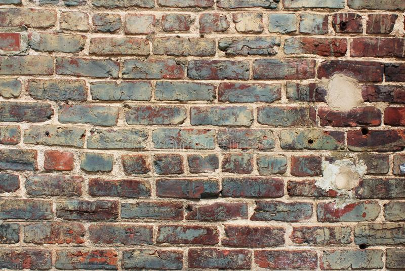 Błękitny i czerwieni glazurujący bolał ściana z cegieł z rocznik cegłą i łatał punkty fotografia stock
