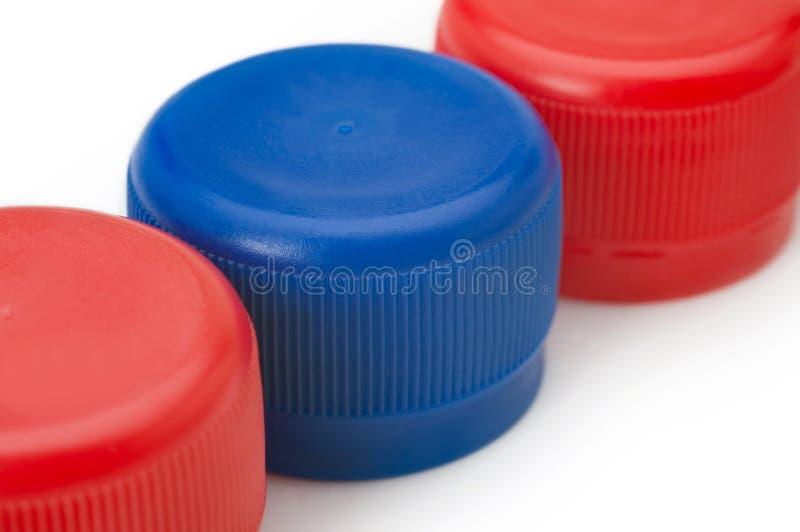 B??kitny i czerwony plastikowy butelek nakr?tek zbli?enie zdjęcie stock