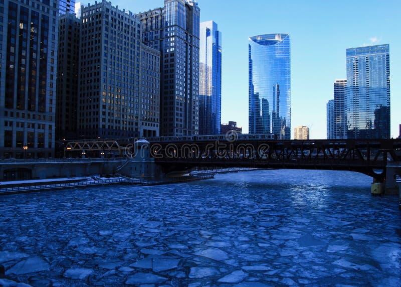 Błękitny i oziębły zima ranek w Chicago podczas gdy el pociągu przepustki nad Chicagowską rzeką i budynkami odbijają pejzaż miejs fotografia royalty free