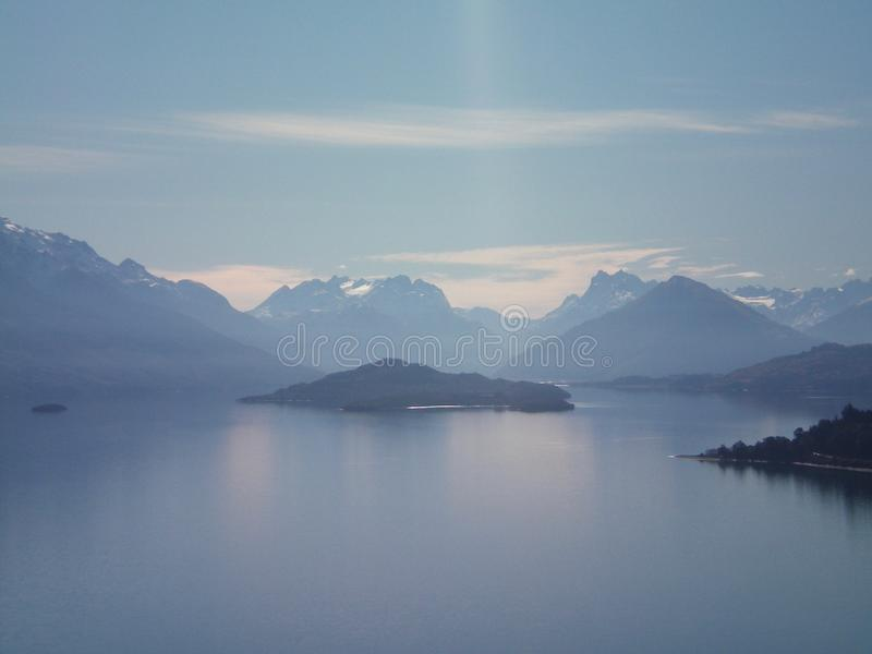 Błękitny jezioro otaczający górami zdjęcie stock