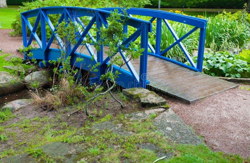 Błękitny mały most nad rzeczną strumień zatoczką w ogródzie. Natura. fotografia royalty free