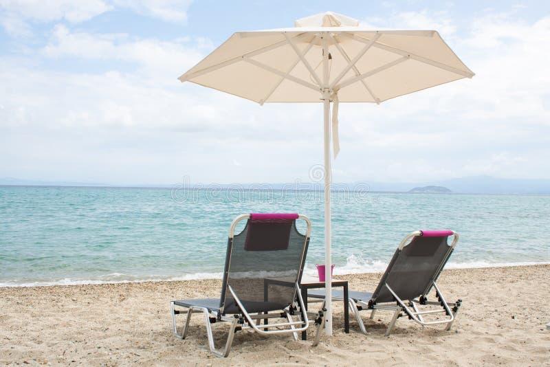 Błękitny morze i biały piasek wyrzucać na brzeg z plażowymi krzesłami i parasolem, Gr obraz royalty free
