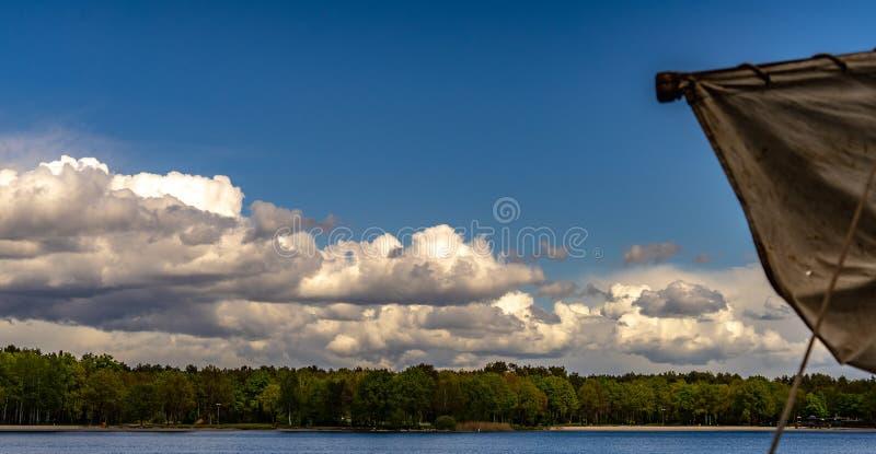 Błękitny niebo nad jeziorem z lasem na brzeg w przedpole specjalnie zamazującym żaglu mała łódka, zdjęcie royalty free