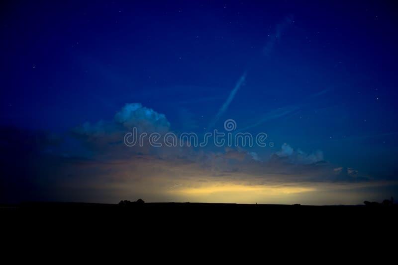 Błękitny nocne niebo z gwiazdami i chmurami nad sylwetka krajobrazem obrazy royalty free