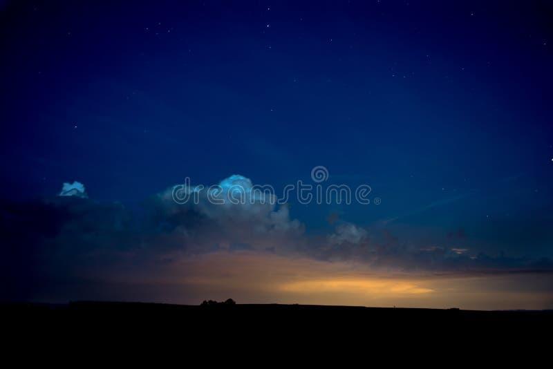 Błękitny nocne niebo z gwiazdami i chmurami nad sylwetka krajobrazem zdjęcia stock