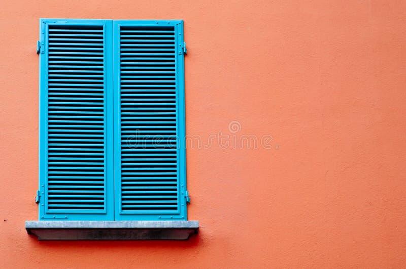 Błękitny okno na pomarańcze ścianie obraz royalty free