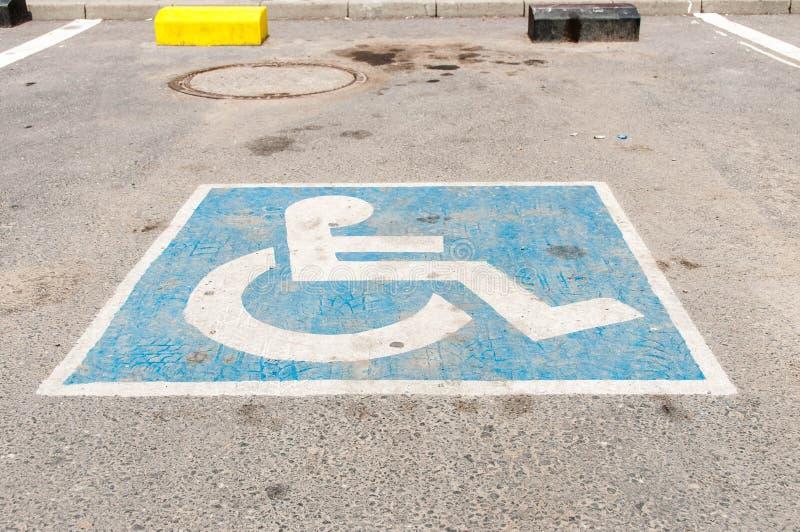 Błękitny parking znak na asfalcie dla niepełnosprawnych persons zdjęcie stock