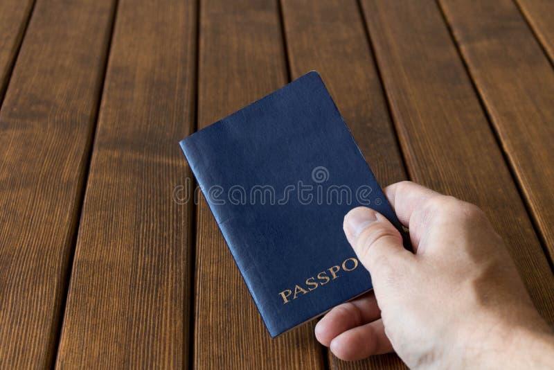 Błękitny paszport w ludzkiej ręce na drewnianym tle Podróży concep obraz royalty free