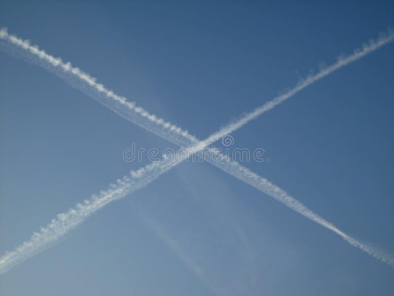 Błękitny pogodny niebo krzyżujący z białymi samolotowymi śladami fotografia royalty free