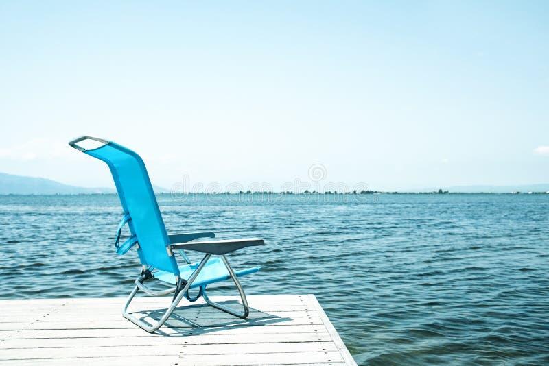 Błękitny pokładu krzesło na drewnianym molu zdjęcia stock