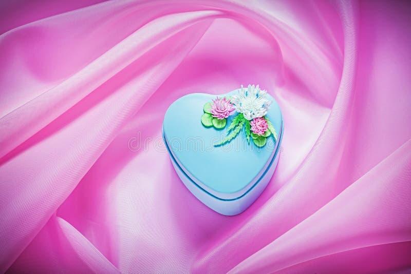 Błękitny prezenta pudełko z kwiatami na różowych tkaniny tła wakacjach co zdjęcie stock