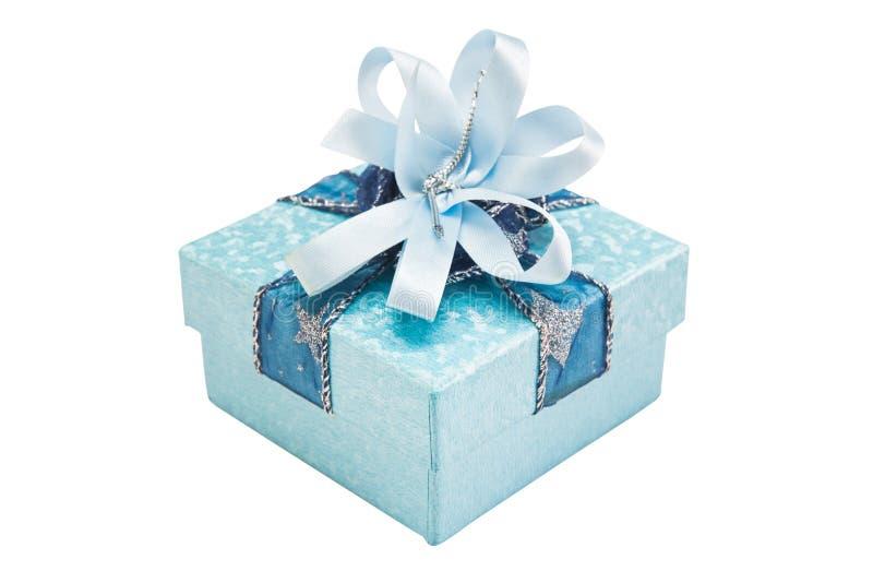Błękitny prezenta pudełko z złocistym i czerwonym tasiemkowym łękiem, odosobnionym na białych półdupkach fotografia stock