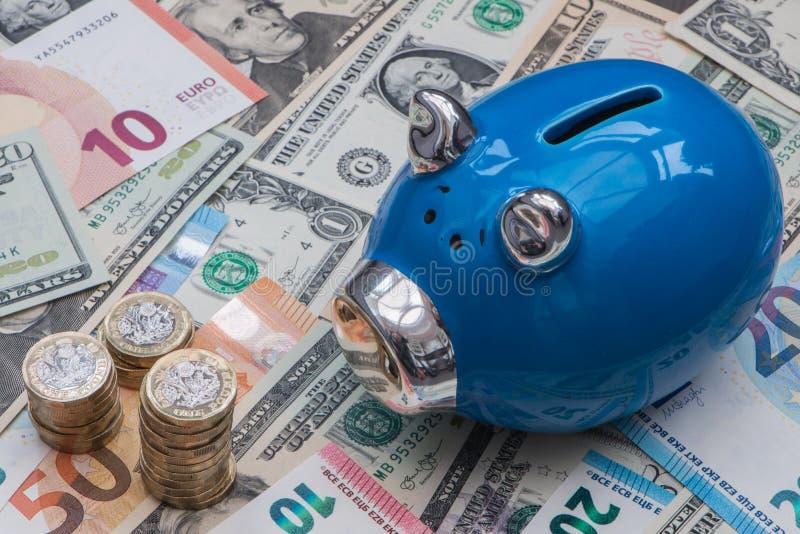 Błękitny prosiątko bank z euro, dolarami i Funtowymi monetami, zdjęcia royalty free