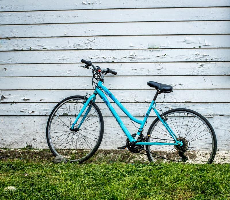 Błękitny rower przeciw białej ścianie zdjęcia stock